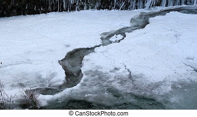 Water Flowing along Frozen Creek in Deep Freeze Winter...