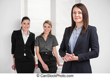 Smiling confident middle aged business woman leading young female business team. Standing together in bright modern office