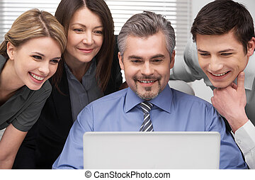 Close up of Smiling group of people looking at laptop...