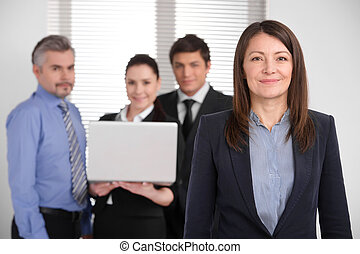 Successful smiling middle age woman looking at camera. Group of business people making blur background