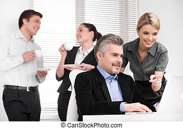 Smiling attractive blond assistant pointing with finger at...