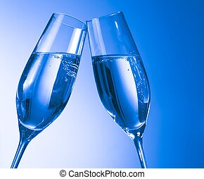 a pair of champagne flutes with golden bubbles on blue light...