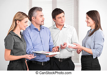 Beautiful middle aged female shearing her opinion with business team. Stylish successful business people in modern office