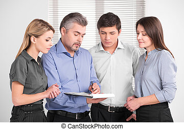 Handsome adult business man showing something on documents. Standing together in bright modern office