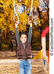 Boy hanging on the rings