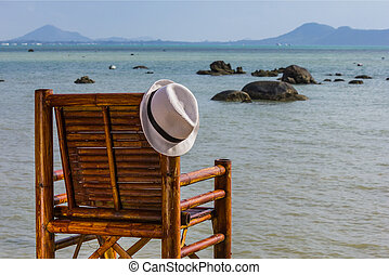Hat hangs on a chair on the background of the sea