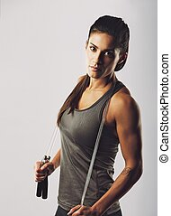 Female athlete posing with jumping rope - Confident young...