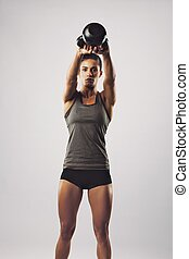 Crossfit female working out with kettle bell - Pretty young...
