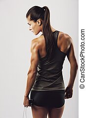 Female bodybuilder holding skipping rope - Rear view image...