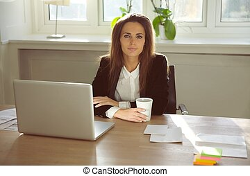 Beautiful young woman sitting in her home office
