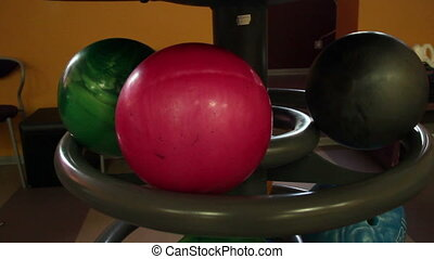 Black bowling ball rolling towards the other two bowling...
