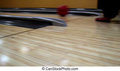 Red bowling bowl set to hit the pins that are arranged. The...