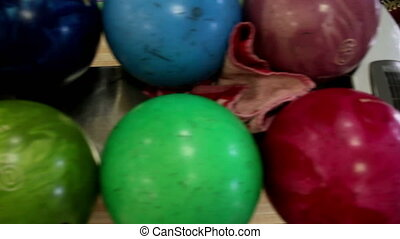 Several bowling balls in set and one violet bowling ball...