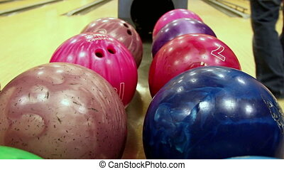 Multi-colored bowling balls where you can see two players...
