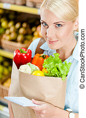Reading list of products girl hands bag with fresh vegetables against the shelves of fruits in the store