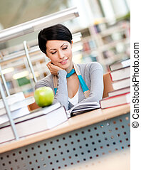 Female student studies sitting at the desk - Female student...