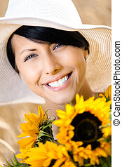 Close up of woman with sunflowers in the field - Close up of...