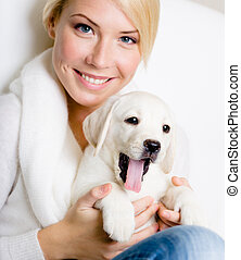 Close up of woman with labrador puppy on her knees - Close...