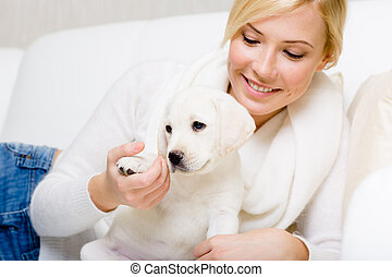 Woman is on the sofa with white puppy - Woman is on the...