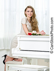 Portrait of female pianist standing near the piano -...