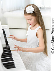 Portrait of little girl in white dress playing piano....