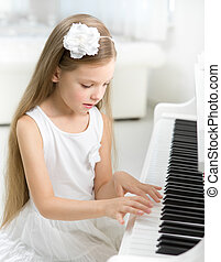 Portrait of little child in white dress playing piano -...