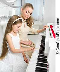 Teacher teaches little girl to play piano - Tutor teaches...