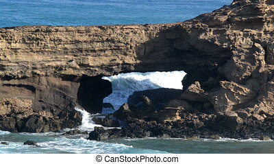 wave crash into lava cave 11092 - Big waves crushing into a...