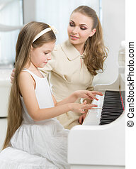 Tutor teaches little child to play piano - Master teaches...