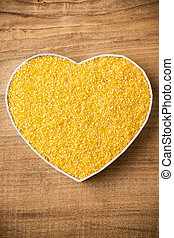 Millet. - Millet, a heart-shaped box. Wooden surface.