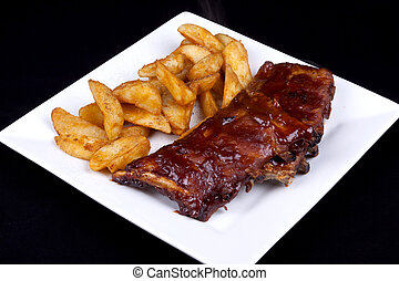 bbq ribs - BBQ ribs with potato wedges on a white plate