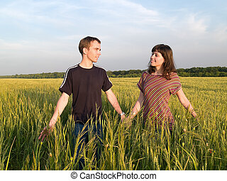 Young Couple Walking Field Holding Hands looking each other