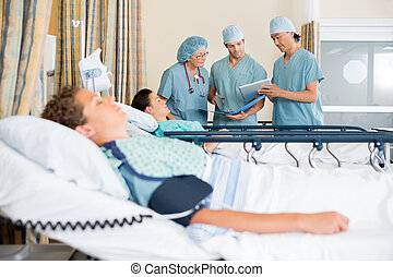 Nurses Discussing Patient's Chart Post Surgery - Team of...