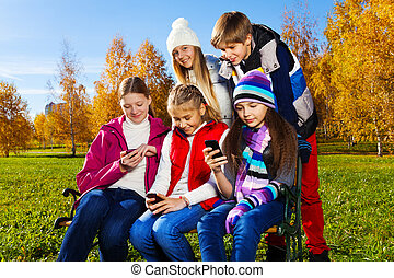 Teens occupied with phones - Group of 5 school age teen kids...