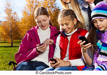 Teen kids busy with cell phones - Close portrait of school...