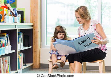 Teacher With Cute Girl Reading Book In Library - Mature...