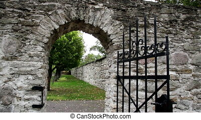 Stone entrance with an old medieval black steel gate - Stone...