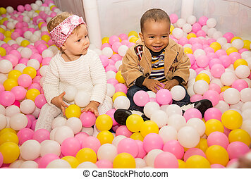Happy children in colored ball on birthday on playground....