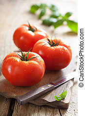 fresh tomatoes on cutting board - fresh tomatoes on cutting...