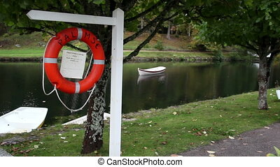 Life preserver hanging and some white bench near the lake....