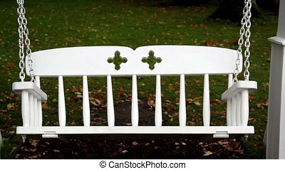 White metal bench swing swinging non stop and has a floral...