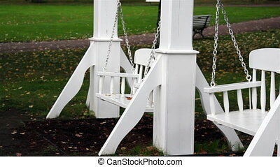 Two bench swings swinging endlessly and is painted in white.