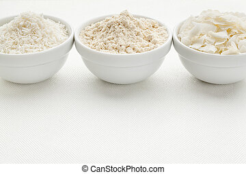 coconut flour and flakes in three white ceramic bowls on...