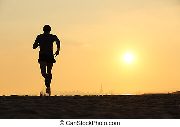 Back view of a man running on the beach at sunset