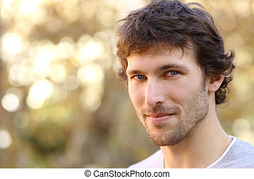 Facial portrait of an attractive adult man with an unfocused...