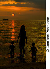 Mother and her kids silhouettes on beach at sunset