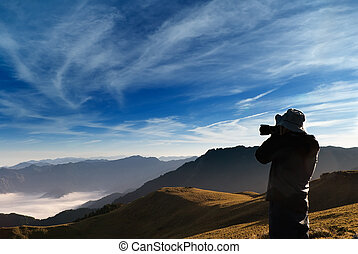 A cameraman standed and shot whith clouds in the outdoor.