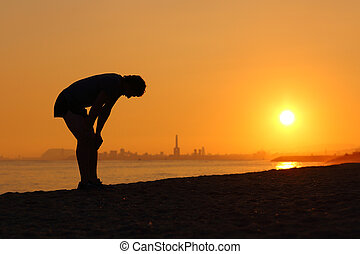 Silhouette of an tired sportsman at sunset with a city in...