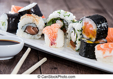 Different types of Sushi on a plate against wooden...