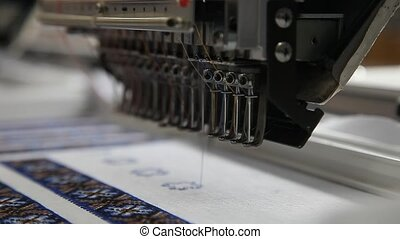 Sewing machine embroiding on fabric